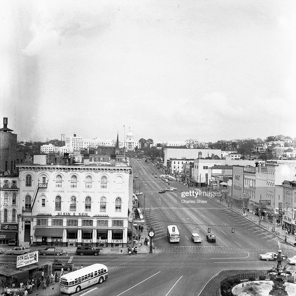 Elevated view along Dexter Avenue, as seen from the Exchange Hotel, towards the Alabama State Capitol where people gather to listen to speakers at the end of the Selma to Montgomery March, Montgomery, Alabama, March 25, 1965. In the foreground is the 'Historic Artesian Basin' where several segregationists display American and Confederate flags.