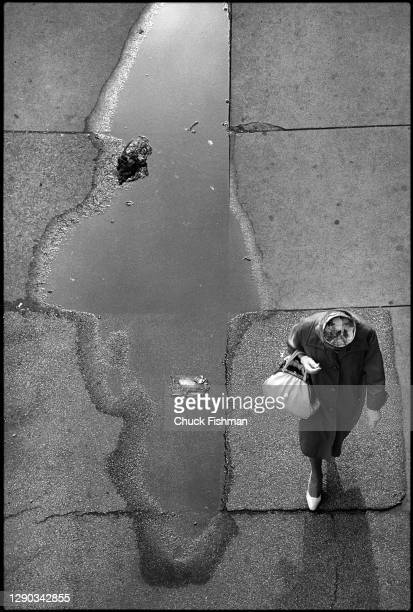 Elevated view along of a woman as she walks past a sidewalk puddle, Chicago, Illinois, June 1978.