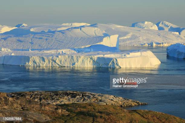 elevated view at a red ship close to huge icebergs in the icefjord - rainer grosskopf stock pictures, royalty-free photos & images
