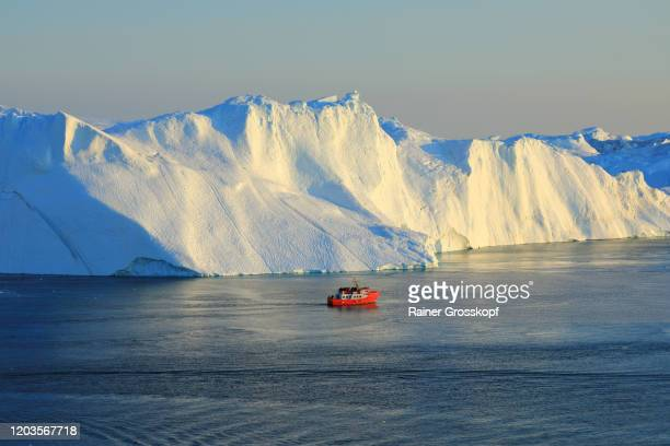 elevated view at a red ship close to huge icebergs in the icefjord - rainer grosskopf foto e immagini stock