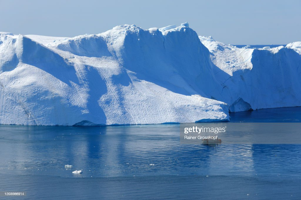 Elevated view at a small ship passing a huge iceberg in arctic sea : Stock-Foto