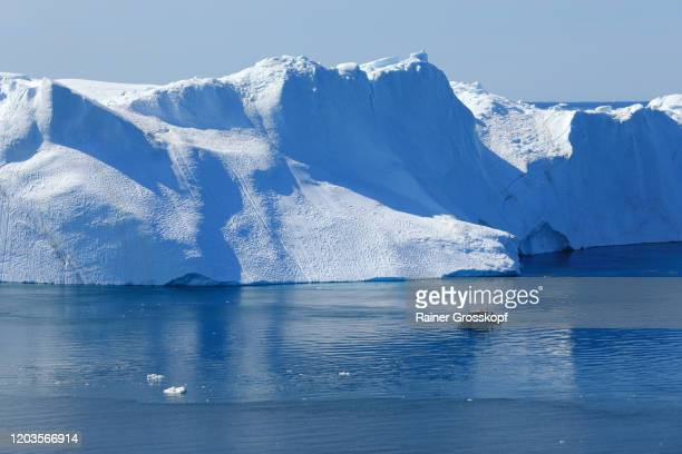 elevated view at a small ship passing a huge iceberg in arctic sea - rainer grosskopf stockfoto's en -beelden