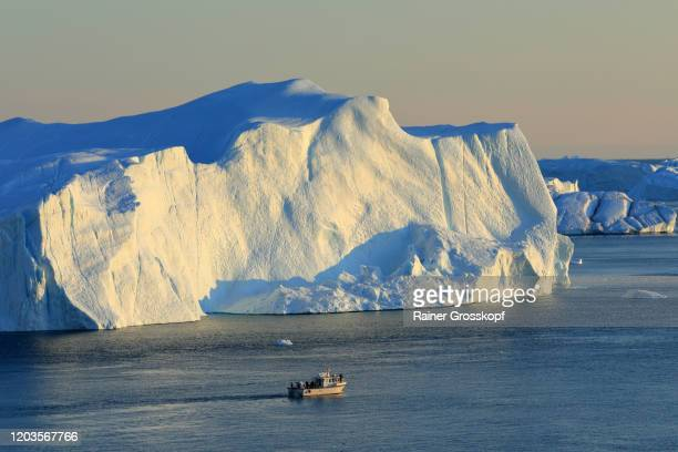 elevated view at a small ship passing a huge iceberg in arctic sea - rainer grosskopf foto e immagini stock