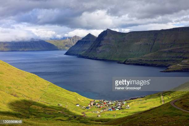 elevated view at a small village situated at the coast of a fjord surrounded by steep mountains - rainer grosskopf stock-fotos und bilder