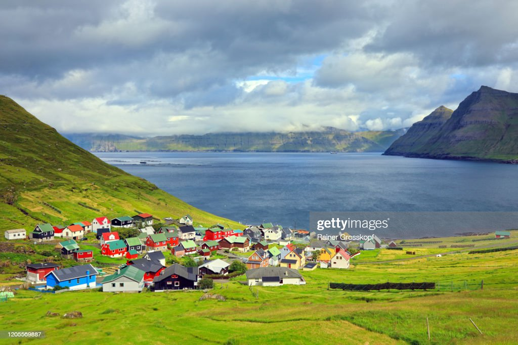 Elevated view at a small village situated at the coast of a fjord surrounded by steep mountains : Stock-Foto