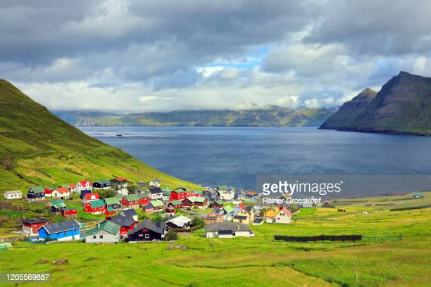 elevated view at a small village situated at the coast of a fjord surrounded by steep mountains - rainer grosskopf stock pictures, royalty-free photos & images