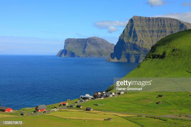 elevated view at a village surrounded by grassy hills sitting on the edge of a cliff above the sea - rainer grosskopf stockfoto's en -beelden