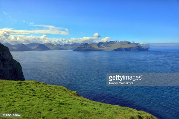 elevated view from a grassy mountain at the sea with cloud covered islands in the far distance - rainer grosskopf stock-fotos und bilder