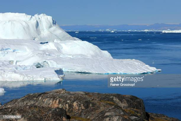 elevated view from rocky terrain at huge icebergs - rainer grosskopf stock pictures, royalty-free photos & images