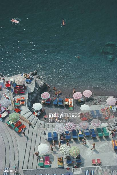Elevated view looking down on sunbathers and parasols on the beach at La Scogliera beach in Positano Italy 1979