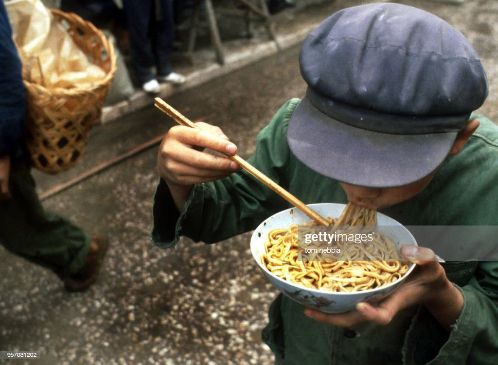 Elevated view of a boy as he eats noodles from a bowl in the street market, Shanghai, China, April 1980.
