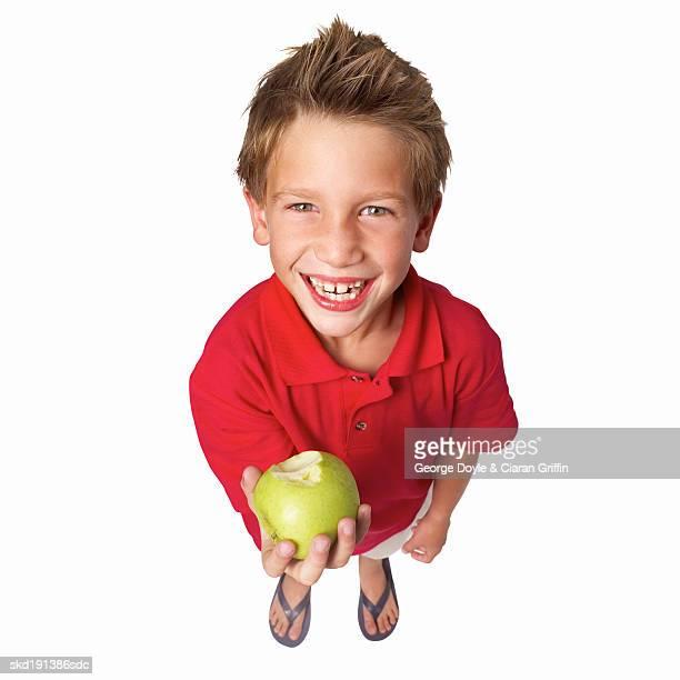 elevated view of a boy (10-11) holding apple - nur jungen stock-fotos und bilder