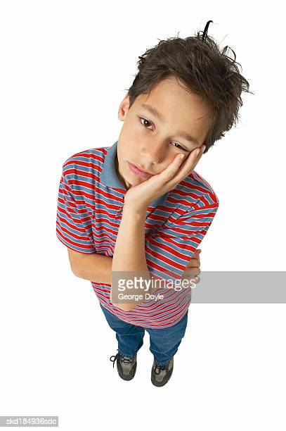 elevated view of a boy (11-12) with his hand touching his face - 12 13 jaar stockfoto's en -beelden