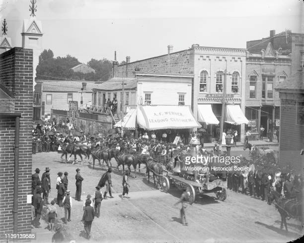 Elevated view of a crowd gathered at the intersection of First and Main Streets to watch a bell wagon pass in a circus parade, probably the Ringling...