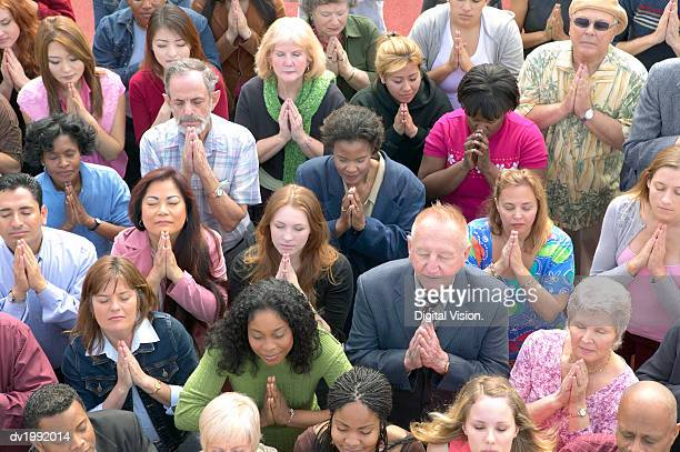 elevated view of a crowd of people praying - praying stock pictures, royalty-free photos & images