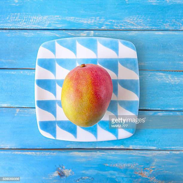 Elevated view of a fruit on a plate. Blue wooden background.