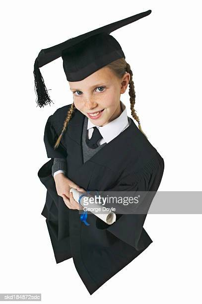 elevated view of a girl (11-12) wearing cap and gown and holding a certificate