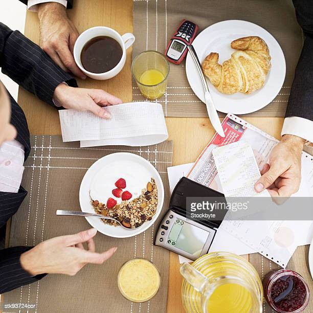 elevated view of a husband and wife discussing bills at a breakfast table