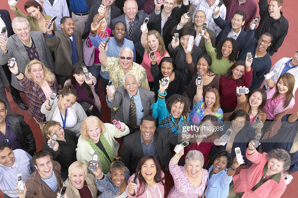 Elevated View of a Large Crowd of Smiling People Holding Mobile Phones in the Air : Stock Photo