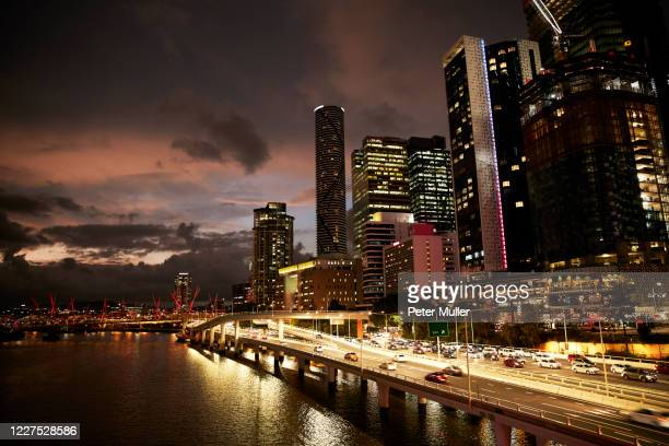 elevated view of a major roadway and traffic leaving the city of brisbane at night. - brisbane stock pictures, royalty-free photos & images