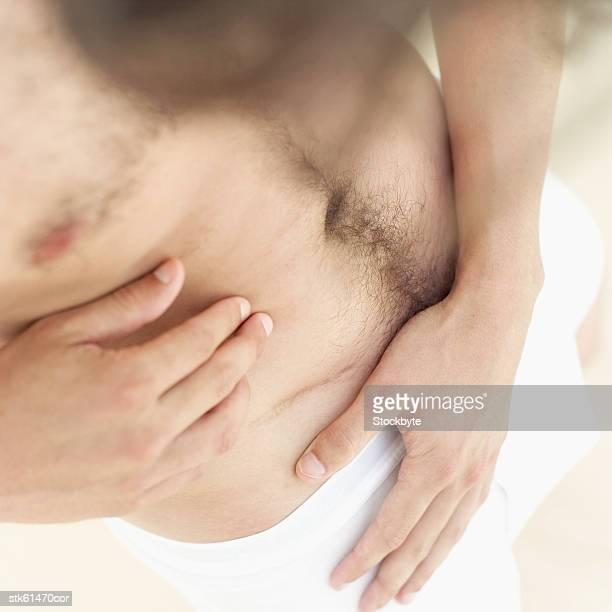 elevated view of a man looking at a scar on his stomach