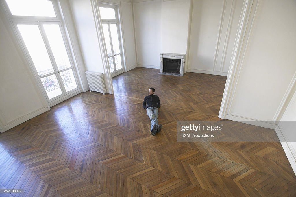 Elevated View of a Man Lying in an Empty Room with a Wooden Floor : Stock Photo