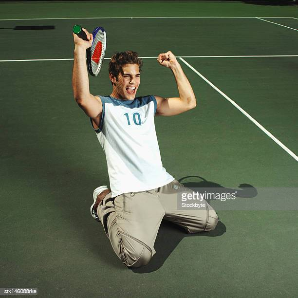 elevated view of a man on his knees in a tennis court celebrating his victory