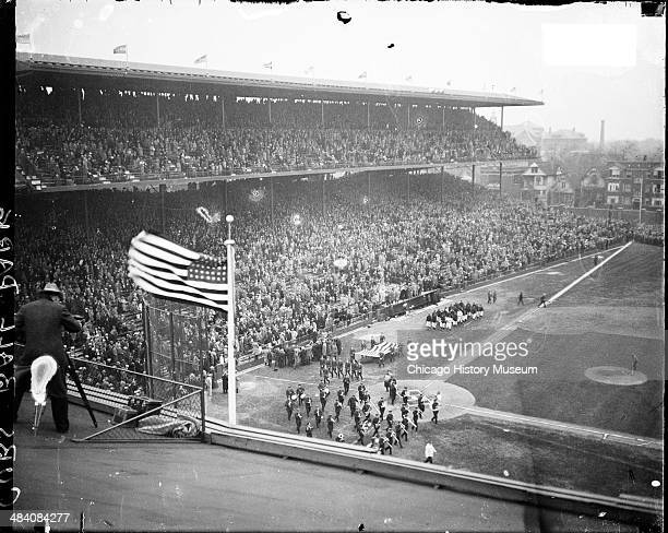 Elevated view of a marching band and people carrying a large American flag at Wrigley Field located at 1060 West Addison Street Chicago Illinois 1927