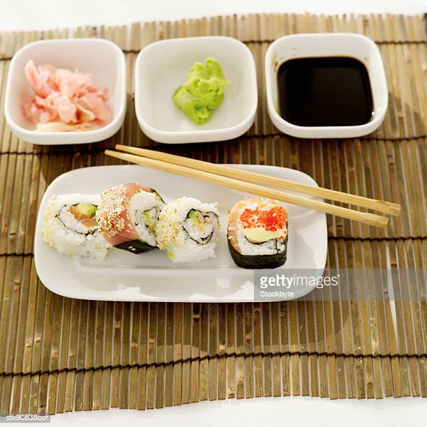 elevated view of a platter of assorted sushi rolls served with condiments - pickled ginger stock pictures, royalty-free photos & images