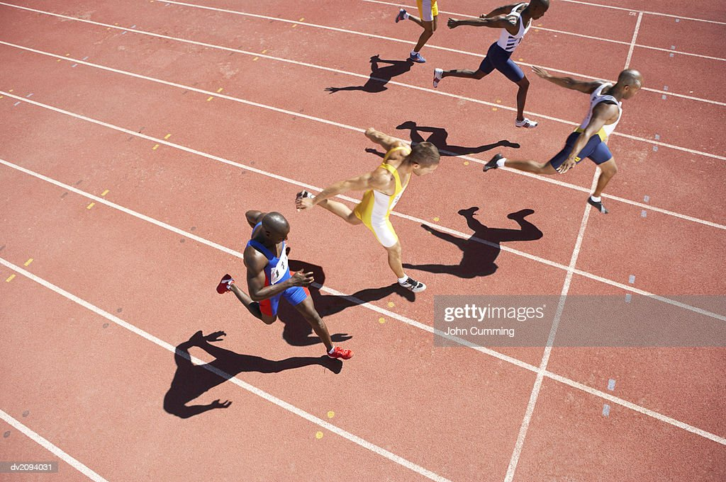 Elevated View of a Sprinter Crossing the Finishing Line on a Running Track : Stock Photo