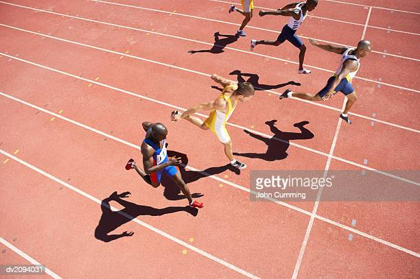 elevated view of a sprinter crossing the finishing line on a running track - finish line stock pictures, royalty-free photos & images