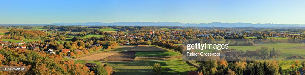 Elevated view of a typical bavarian small town with a prominent church in autumn and the Alps in the background : Stock Photo