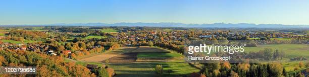 elevated view of a typical bavarian small town with a prominent church in autumn and the alps in the background - rainer grosskopf stock-fotos und bilder