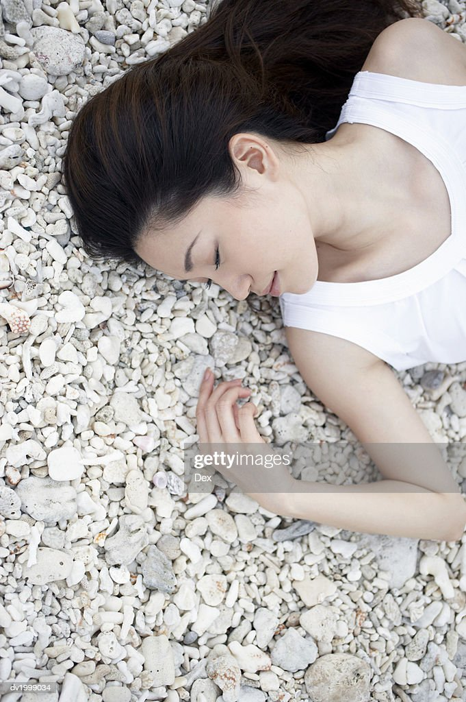 Elevated View of a Woman Lying on Pebbles With Her Eyes Closed : Stock Photo