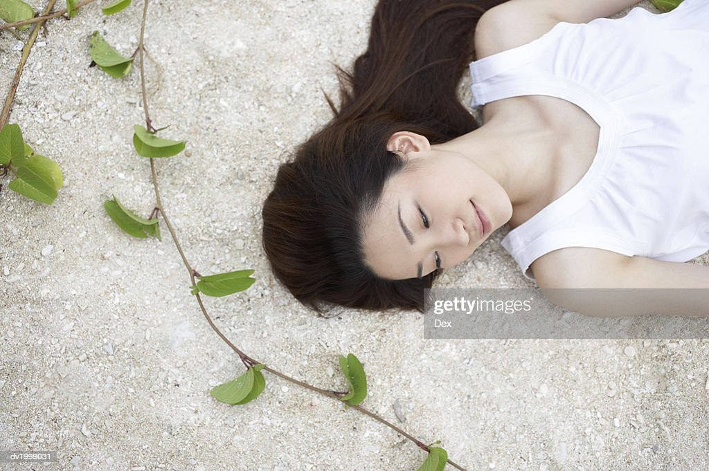 Elevated View of a Woman Lying on Sand : Stock Photo