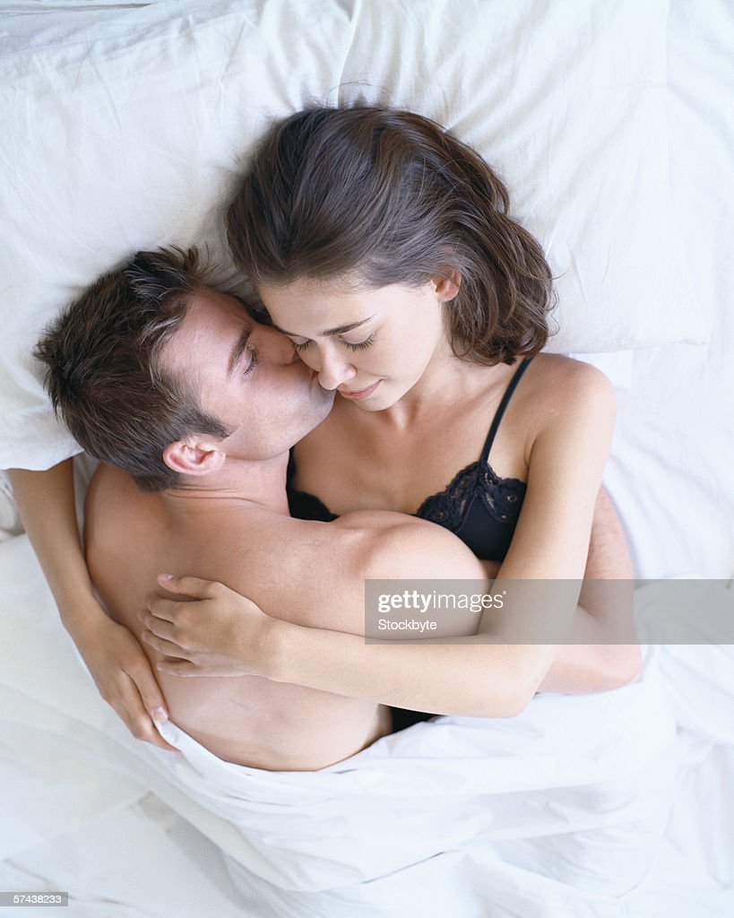 Elevated view of a young couple holding each other in bed