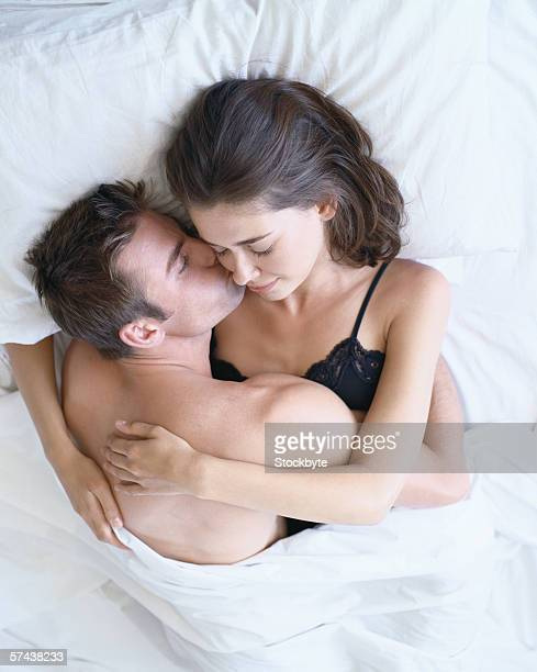 elevated view of a young couple holding each other in bed - kissing stock pictures, royalty-free photos & images