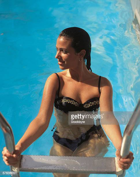 elevated view of a young woman climbing up a swimming pool ladder - capelli neri foto e immagini stock