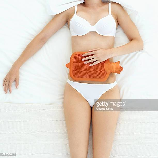 Elevated view of a young woman lying in bed with a hot water bottle on her stomach
