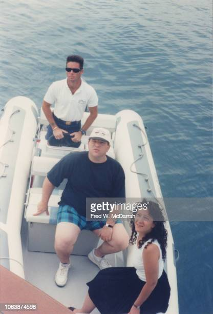 Elevated view of American film producer Harvey Weinstein and public relations director Julie Polkes as they sit with an unidentified man in a dinghy...