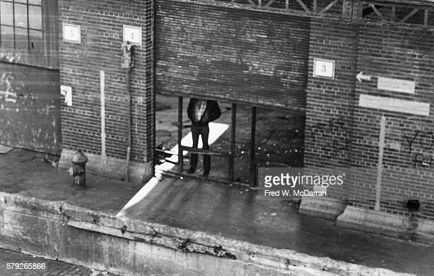 Elevated view of an unidentified man as he stands behind the partially closed roller shutter of a derelict waterfront building New York New York...