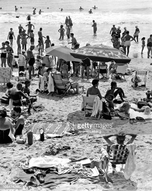 Elevated view of beachgoers as they sunbath on the sand and swimming in the surf at Coney Island Beach Brooklyn New York New York 1950