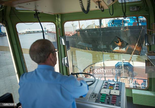 Elevated view of captian in bridge steering tugboat into harbour