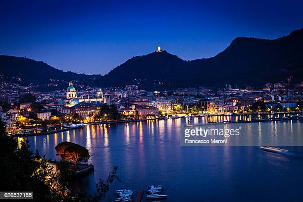 Elevated view of city lights at night on lake Como, Como, Lombardy, Italy