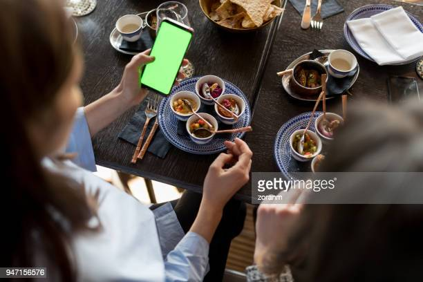 Elevated view of coworkers in restaurant using smart phone with green screen