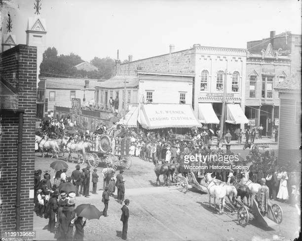 Elevated view of crowd gathered at the intersection of First and Main Streets to watch a calliope and chariot riders in a circus parade, probably the...