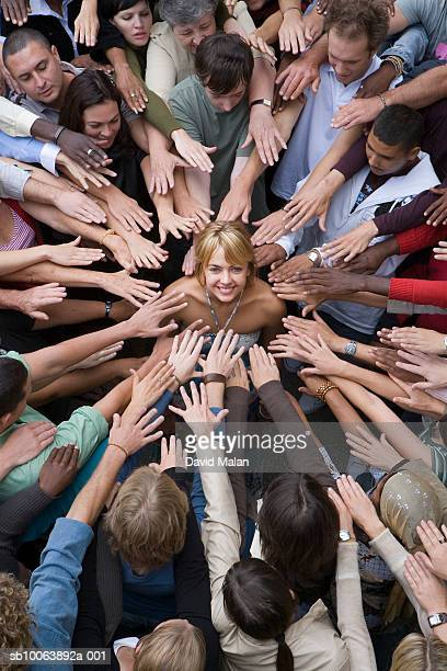 elevated view of crowd surrounding woman, reaching toward her - surrounding stock pictures, royalty-free photos & images