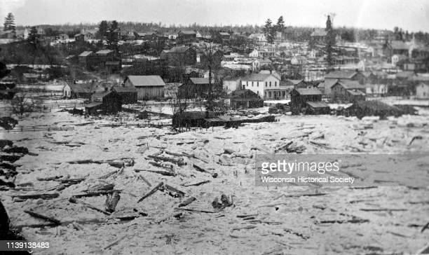 Elevated view of damage to buildings after the 1911 flood of the Black River Black River Falls Wisconsin 1911 Wooden debris is floating in the flood...