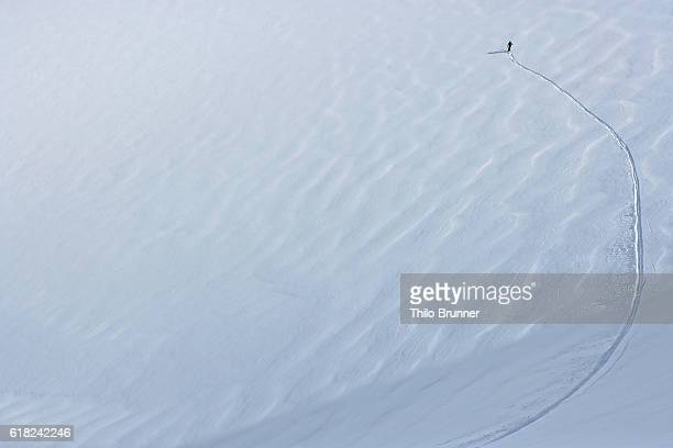Elevated view of distant skier and ski track on snow