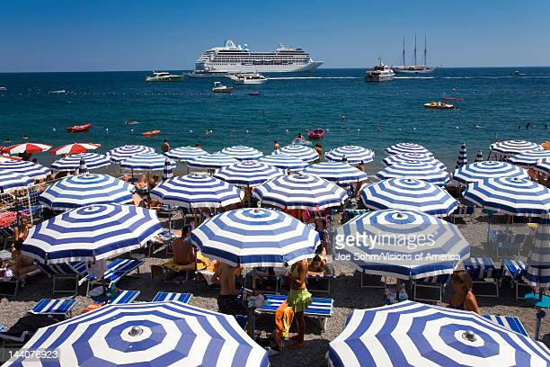 Elevated view of famous beach umbrellas of Amalfi with cruise ship in background in the province of Salerno Amalfi Italy Europe